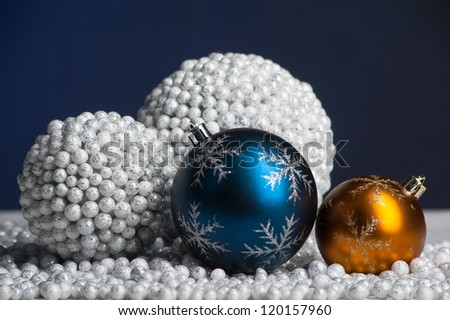 Blue and yellow christmas decoration on artificial snow on blue background - stock photo