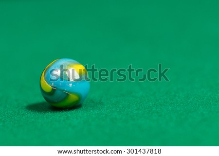 Blue and yellow Colorful Marble Ball on Green background - stock photo