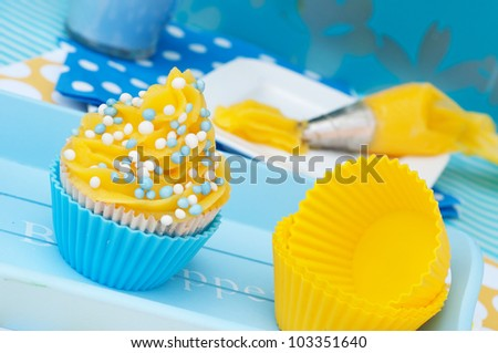 Blue and yellow cupcake on a plateau with empty cups - stock photo