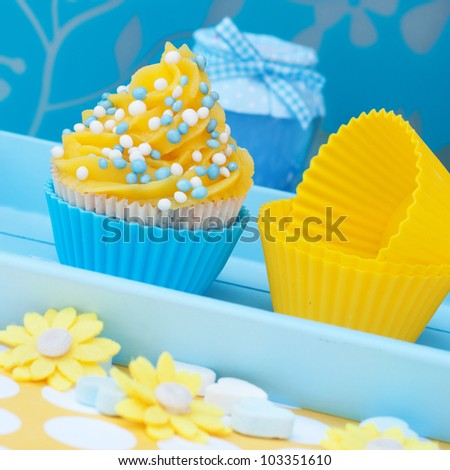 Blue and yellow cupcake setting with flowers - stock photo