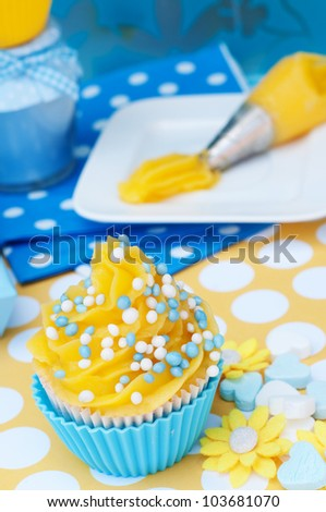 Blue and yellow cupcake setting with whipped cream and rusk - stock photo