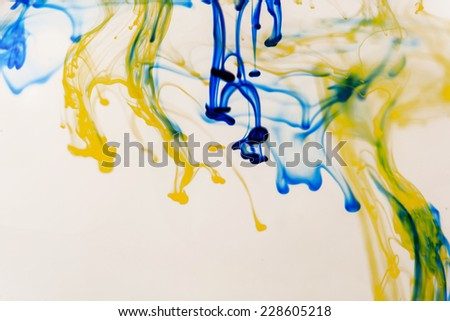 Blue and yellow liquid in water making abstract forms  - stock photo