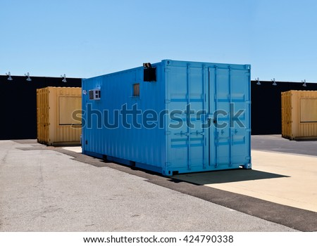 Blue and yellow mobile shipping containers in industrial site
