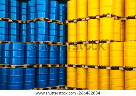 Blue and yellow oil drums in a factory - stock photo