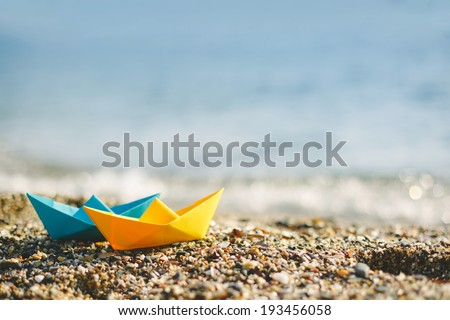 Blue and yellow paper boats on beach outdoors  - stock photo