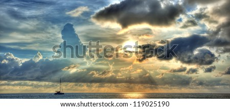 Blue and yellow sunset panorama over ocean with yacht silhouette - stock photo