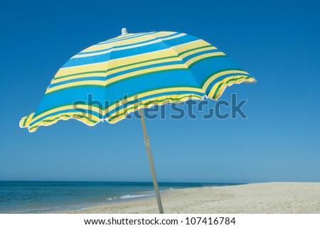 Blue and yellow umbrella on a desert sandy beach - stock photo