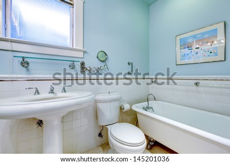 Blue antique elegant bathroom with white tub and tile.