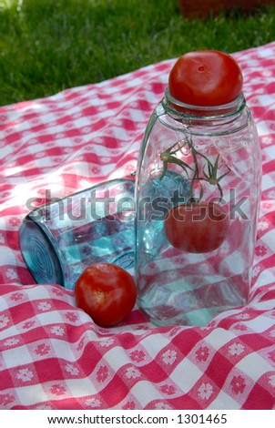 Blue antique glass jars used for canning fruits and vegetables, sitting on a vintage table cloth with three tomatoes. - stock photo