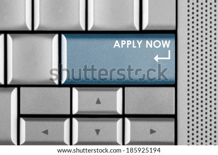 Blue Apply now key on a computer keyboard with clipping path around the Apply now key - stock photo
