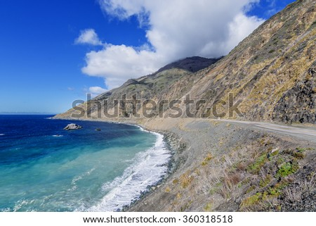 Blue & aquamarine sea & sky, white clouds, waves splashing on huge rocks, desolate road to nowhere, along a rocky coastline, traveling the Big Sur Highway (Highway 1) on the California Central Coast. - stock photo