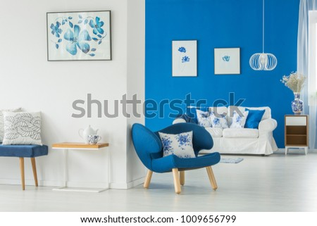 Blue Armchair Next To A Table In Bright Living Room Interior With White  Settee Against Blue