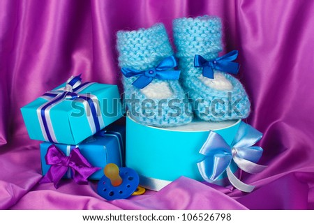 blue baby boots, pacifier, gifts on silk background - stock photo