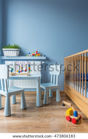 Blue baby room with floor panels, cot and small blue table and chairs