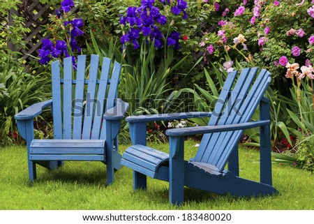 Blue back yard lawn chairs surrounded by a garden of flowers.  - stock photo
