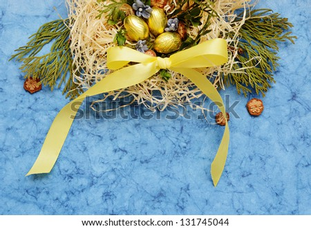Blue background and arrangement with golden eggs and nest in the top - stock photo