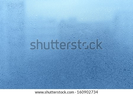 Blue background with natural water drops on glass - stock photo