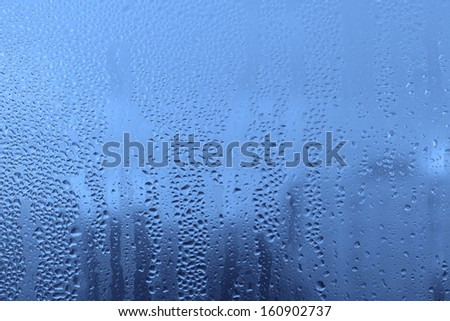 Blue background with natural water drops on glass