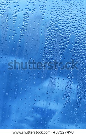 Blue background with water drops on glass