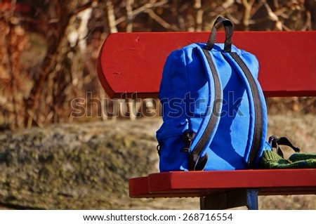 Blue backpack on the red bench - stock photo
