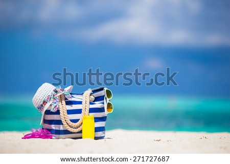 Blue bag, straw white hat, sunglasses, flip flop and sunscreen bottle on tropical beach