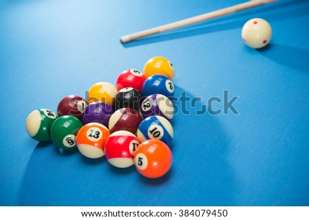 Blue baize cloth pool table with the balls and cue stick.