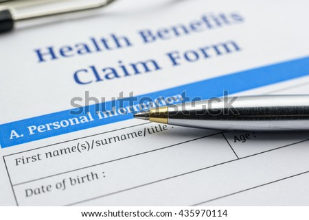 Blue ballpoint pen and a health benefits claim form on a clipboard. A blank / empty form is waiting to be filled and signed by patient / insured person. - stock photo