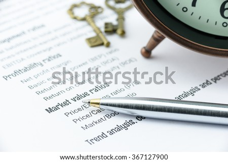 Blue ballpoint pen on a financial ratios analysis check lists with an antique clock and two vintage brass keys. Financial, business and investment analysis concept.