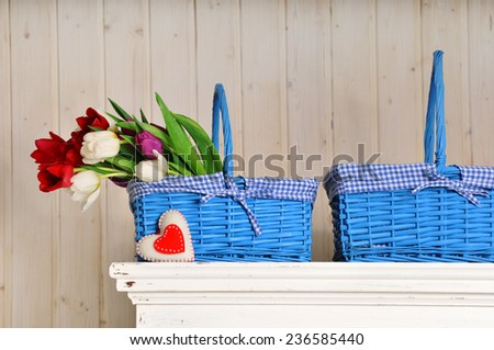 Blue basket with flowers and plush heart - stock photo