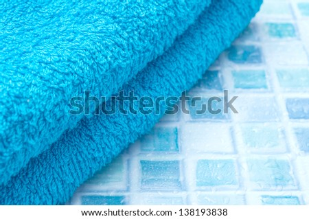 Blue Bath Towels on Blue Bathroom Tiles - stock photo