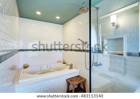 Blue bathroom interior with white tile trim wall, glass cabin shower and bath tub. Northwest, USA