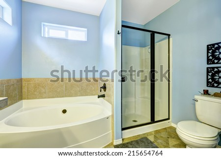 Blue bathroom with tile trim and glass door shower