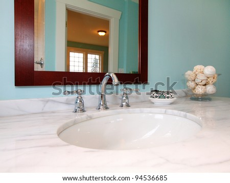 Blue bathroom with white marble sink. - stock photo