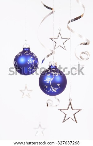 Blue baubles with the silver stars on the white background