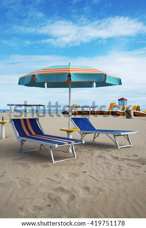 Blue beach chairs and umbrella, Rimini, Italy - stock photo