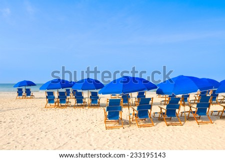 Blue beach chairs and umbrellas at a tropical resort.