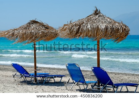 blue beach chairs with a beautiful view of the tropical, turquoise ocean under a straw umbrella on white sandy beach - stock photo