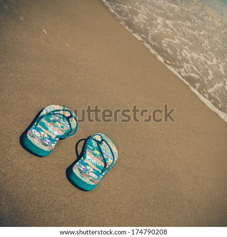 Blue beach slippers on sandy beach with copy space for text, summer, bathing - vintage coaster - stock photo