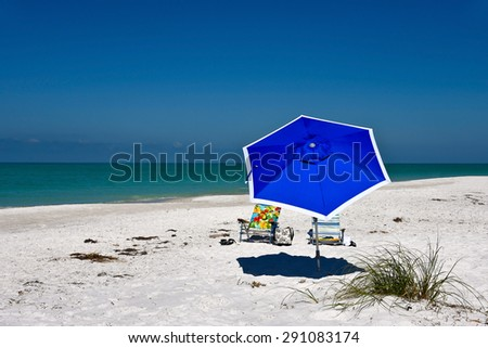 Blue Beach Umbrella and Two Chairs on the Beach  - stock photo