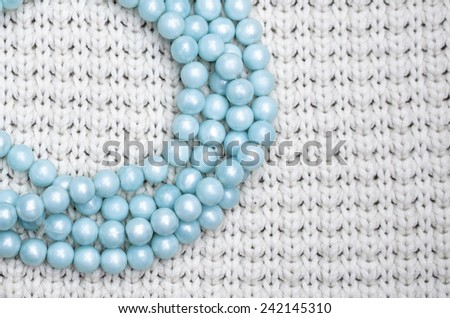 blue beads on knitted background - stock photo