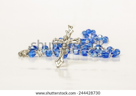 Blue beads rosary with silver cross isolated on the bright background - stock photo