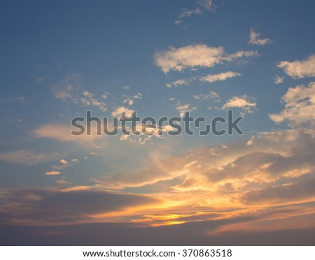 Blue, beautiful sky with white, orange, puffy clouds