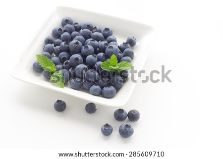 blue berries in white plate on white background