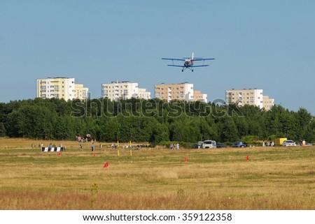 blue biplane over the city - stock photo