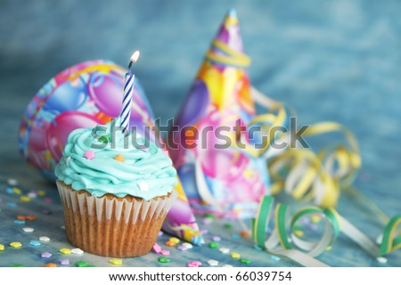 Blue birthday cake with candle on top and hat and twinkle in the background - stock photo