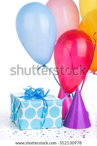 Blue birthday present with party hats and balloons on a white background