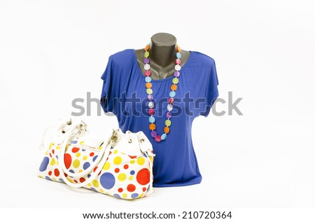 Blue blouse on mannequin with matching accessories. Elegant blouse on tailor's dummy with matching colorful purse and necklace - stock photo