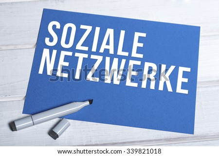 blue board with german words social networks written in white and black marker lying on top