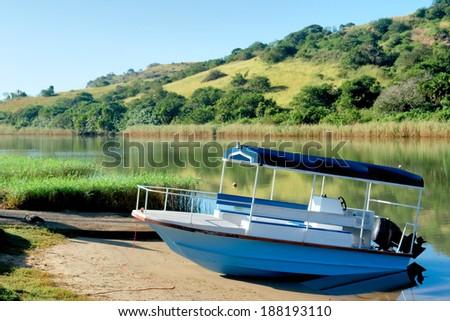 Blue boat on morning river. Shot in Port Edward, Kwazulu-Natal, South Africa. - stock photo