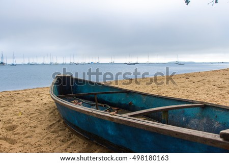 Blue boat on the beach sand on a cloudy day - Florianopolis, Brazil